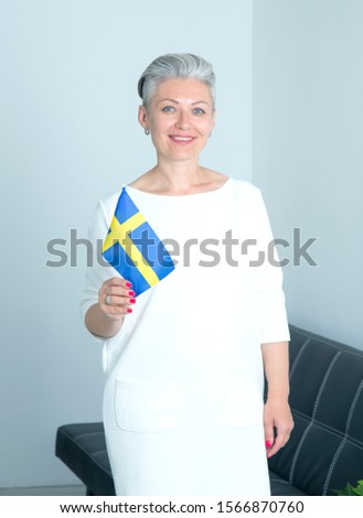 Mature woman with Sweden flag standing in office. Short haired female with gray hair.
