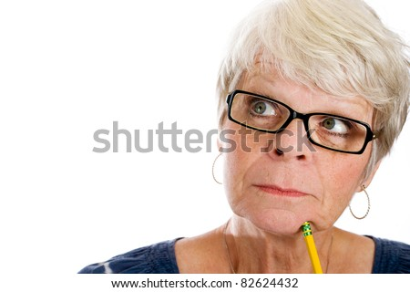 Mature woman with white hair and glasses looking up with a pencil under her chin.
