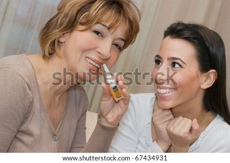stock photo : Mature woman with young beautiful daughter smelling perfume.