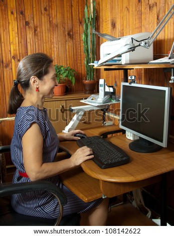 Mature woman working at personal computer at home