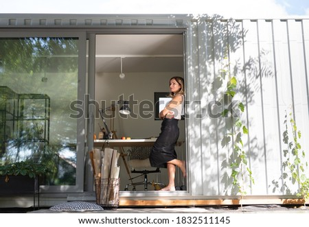 Mature woman working in home office in container house in backyard, resting. Foto stock ©