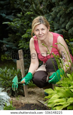 Mature woman works in her garden using some tools
