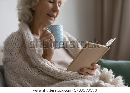 Mature woman wrapped in warm knitted plaid relax on couch drink tea, read favourite book, classic literature, enjoy carefree time on weekend, close up. Pastime and hobby, tranquil retired life concept Stock photo ©