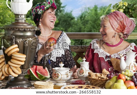 Mature women from the Victorian era carefree laugh while having a cup of tea. Kustodiev Russian artist style