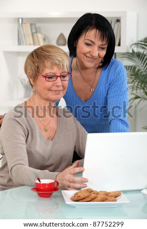 Mature women in front of a notebook at home