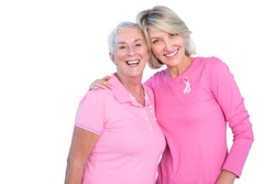 Mature women wearing pink tops and ribbons for breast cancer on white background