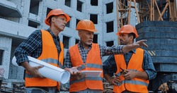 mature worker pointing with hand and talking near coworkers and building crane on construction site