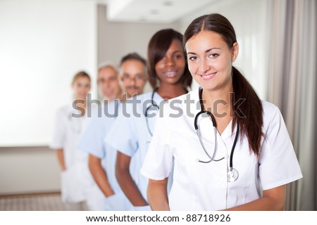 stock photo : Mature young female doctor with group of happy successful ...
