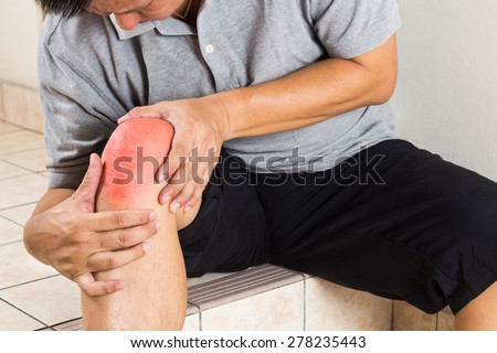 Matured man suffering from painful knee joint seated on steps