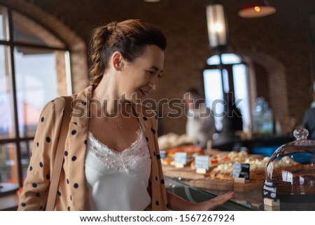 Matured middle aged woman dressed style fasnion clothes chooses the pastry bakery on showcase table in cafe.