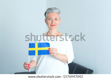 Matured woman with flag of Sweden. Scandinavian female business.