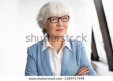 Maturity, age, experience and retirement concept. Confident mature female CEO dressed in stylish formal wear and eyeglasses crossing arms on her chest. Smart senior Caucasian woman posing indoors