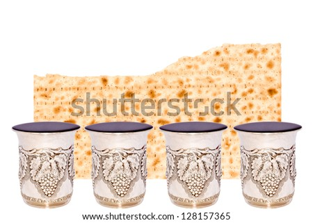 Matzah and four cups of wine for the Passover seder. Half of a broken matzah behind 4 shiny silver kiddush cups filled to the brim with red wine. Room for text. Isolated on a white background.