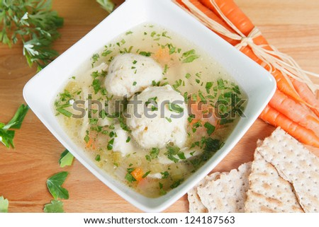 Matzah Ball Soup garnished with carrots and Matzo crackers