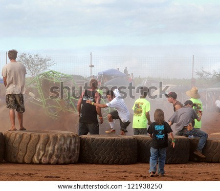 MAUI, HAWAII-DEC 9: Fans scramble to avoid wild rock crawler vehicle at Maui Motorsports Park on December 9, 2012 in Maui, Hawaii.
