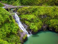 Maui, Hawaii Hana Highway - Wailua Iki Falls (Wailuaiki). Road to Hana connects Kahului to the town of Hana Over 59 bridges, 620 curves, tropical rainforest