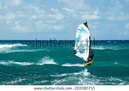 MAUI, HAWAII - SEPTEMBER 17, 2011 - Windsurfer in windy weather on September 15, 2011 in Maui, Hawaii. Windsurfing is a surface water sport that combines elements of surfing and sailing