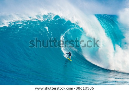 "MAUI, HI - MARCH 13: Professional surfer Carlos Burle rides a giant wave at the legendary big wave surf break ""Jaws"" during one the largest swells of the winter March 13, 2011 in Maui, HI. - stock photo"