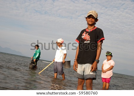 MAUMERE, INDONESIA - AUGUST 8: family fishing urchins in Maumere, Indonesia on August 8, 2010. Seagrass meadows support subsistence fisheries that harvest of sea urchins, small fish and shellfish for local markets - stock photo