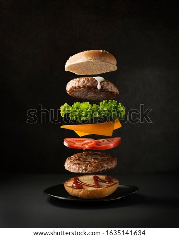 Maxi hamburger with flying ingredients placed on black background. Conceptual jumping Burger. Delicious and attractive hamburger with refreshing ingredients