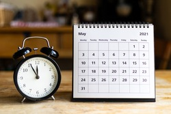 May 2021 calendar - month page showing date and vintage clock on wooden table