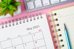 May 2021 calendar with note book on pink background.