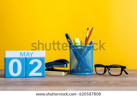 May 2nd. Day 2 of month, calendar on business office table, workplace at yellow background. Spring time