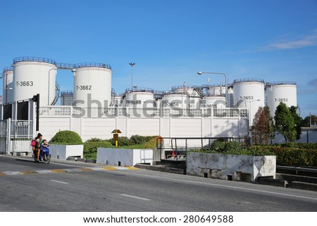 MAY 21, 2015: SRIRACHA, THAILAND. View of landscape in oil refinery plant with fuel storage tanks and piping system with bright blue sky on a sunny day. #280649588