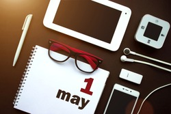 May 1st . Day 1 of month, Calendar date. Office workplace with laptop, notebook, office supplies and stationery on brown back. Spring month, day of the year concept