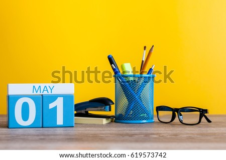 May 1st. Day 1 of month, calendar on business office table, workplace at yellow background. Spring time