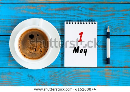 May 1st. Day 1 of month, calendar on white notepad with morning coffee cup at work place background. Top view #616288874