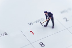 May 1st. Day 1 of month.  Miniature worker standing on Calendar. labor day's concept.