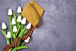 May 9. St. George ribbon, military cap with white tulips on a gray background. The traditional symbol of Victory Day 1945. Victory Day holiday. Postcard. copy space. flat lay.