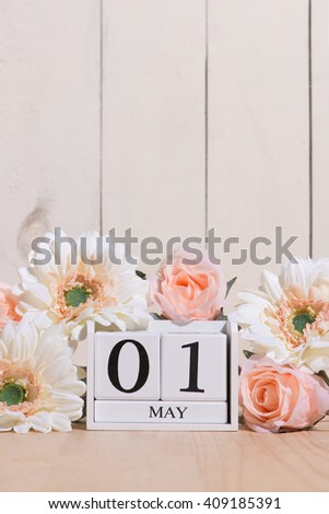 May 1st. Happy May Day white block wood calendar decorated with spring flowers on wood table. #409185391