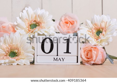 May 1st. Image of may 1 white block calendar on white background with flowers. Spring day, empty space for text. International Workers' Day #409185364