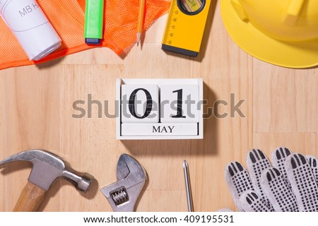 May 1st. Image of may 1 white blocks wooden calendar with construction tools on the table. International Workers\' Day. Labor day concept.