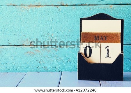 May 1st. Image of may 1 wooden calendar over blue wooden background. Spring day,  International Workers' Day, Happy May Day . room for text #412072240