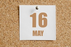 may 16. 16th day of the month, calendar date. White calendar sheet attached to brown cork board. Spring month, day of the year concept.