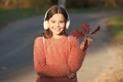 May this autumn be as melodious as happy song. Happy small girl listen to music on autumn landscape. Little child enjoy listening to happy melody. Happy hour starts here