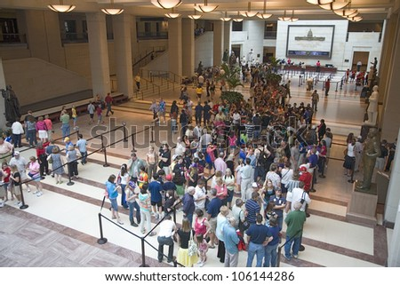 MAY 2009 - Tourists stand in line for tickets with view of U.S. Capitol through glass windows at the U.S. Capitol Visitors Center, Washington, D.C.