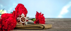May 9, Victory Day holiday. Holiday card with order, St. George ribbon, flowers and military cap. May 9 background, copy space and translation with Victory Day.