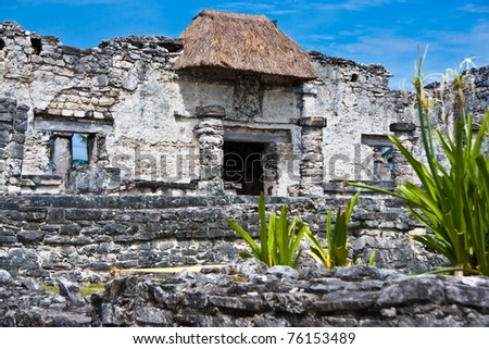 mayan ruins in tulum mexico. dramatic clouds paint a scene of an past time.