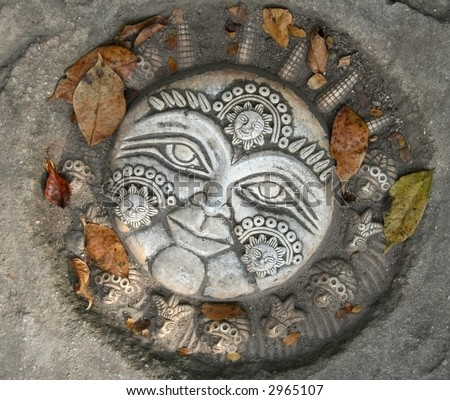 Mayan sun stone sculpture on pavement with leaves