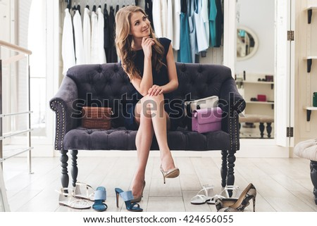 Maybe I need another pair? Beautiful young woman looking thoughtful while sitting on sofa at the clothing store #424656055