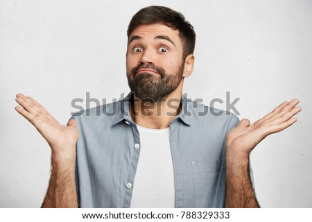 Maybe yes or no. Doubtful bearded fashionable guy shrugs shoulders in bewilderment, tries to make decision, puzzled what he wants, isolated over white concrete wall. Hesitation and uncertainty Stockfoto ©