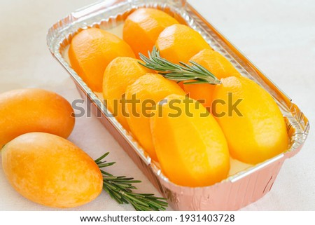 Mayongchid or plum mango or marian plum cheese pie decorated with rosemary put on white table look so delicious. Sweet yellow marian plum cheesecake. Homemade bakery concept with summer fresh fruit.