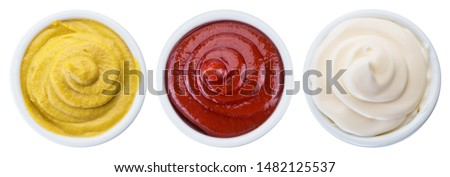 Mayonnaise, mustard and tomato sauces in white bowls. File contains clipping path.