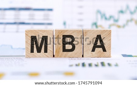 MBA - Master of Business Administration. Wooden letters spelling. MBA writting on wooden cubes on financial documents background