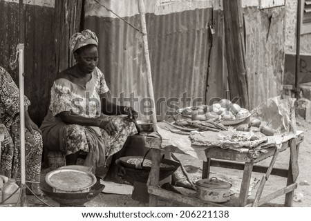 Mbour, Senegal - July 9, 2014: A woman selling food on the street roasts peanuts in a wok on July 9, 2014 in Mbour, Senegal.