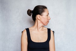McKenzie method exercise to relieve neck pain, a woman gently rotates her head while doing neck pain relief exercises